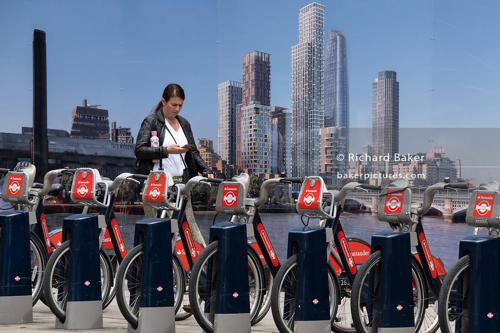 A pedestrian walks past Santander-sponsored rental bikes awaiting riders and lined up in their charging docks in front of a construction hoarding that shows the Southbank skyline, on 22nd June 2021, in London, England.