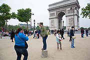 Tourists taking pictures at the Arc de Triomphe. The Arc de Triomphe de l'Etoile is one of the most famous monuments in Paris. It stands in the centre of the Place Charles de Gaulle.
