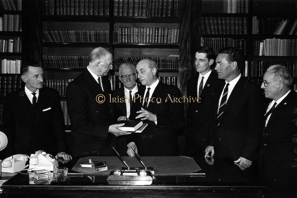 """05/04/1965<br /> 04/05/1965<br /> 05 April 1965<br /> Presentation of books to President Eamon de Valera. Two complete volumes of the """"History of Motion Pictures"""" by Terry Ramsey and Mark Quigley (Jr.), were presented to President de Valera as patron of the Society by the Theatre and Cinema Benevolent Society of Ireland at Aras an Uachtarain. Picture shows the President receiving the volumes from Mr Louis Elliman (right), Chairman of the Society. Also in the picture is Mr Frank Robbins, (centre) Vice-chairman of the Society."""