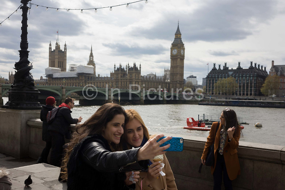 Two young women take a selfie overlooking the River Thames on Londons Southbank with the Palaces of Westminster and Queen Elizabeth Tower containing Big Ben bell in the background. With their smartphone outstretched to take in the panoramic view behind them, the girls smile into the lens with the famous Westminster landmark on the opposite bank of the river. 17.4 million tourists visit the UK capital 2014.