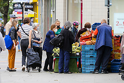 © Licensed to London News Pictures. 09/09/2020. London, UK. Shoppers wearing face coverings and not observing social distancing at a fruit and vegetable stall on Wood Green High Road, in the London Borough of Haringey as the number of COVID19 cases increases. As at Sunday, September 6, the government reported a three-month high in coronavirus cases in England, with 2,988 lab-confirmed cases reported on that day, the highest number of new cases since May. According to the figures published by the COVID-19 Symptom Study app, Newham, has most active cases among London boroughs, with 97 per 100,000 people.<br /> The London Borough of Haringey has 75.7 cases per 100,000 people. Britain could be facing a nationwide curfew as part of the efforts to avoid a second wave. Photo credit: Dinendra Haria/LNP