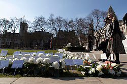 © Licensed to London News Pictures. 22/03/2021. London, UK. Members of the public stand next to flowers and notes that have been placed in Parliament square in memory to those who lost their lives in the 2017 Westminster Bridge terror attack. Today marks four years since the attack and a commemorative plaque is expected to be installed on Westminster Bridge when Coronavirus restrictions are lifted . Photo credit: George Cracknell Wright/LNP