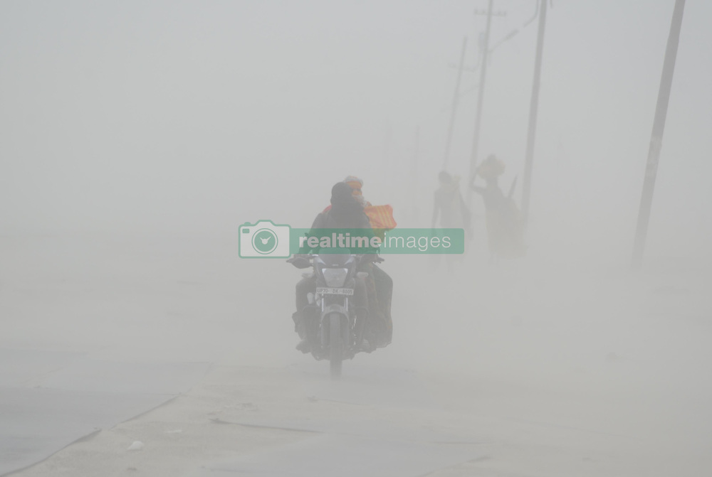 June 16, 2017 - Allahabad, Uttar Pradesh, India - Indian devotee walk through a dust storm at the Sangam, the confluence of the Ganges, Yamuna and mythical Saraswati rivers in Allahabad..The climate of India comprises a wide range of weather conditions across a vast geographic scale and varied topography, making generalizations difficult. India hosts six major climatic subtypes, ranging from arid desert in the west, alpine tundra and glaciers in the north, and humid tropical regions supporting rain forests in the southwest and the island territories. (Credit Image: © Prabhat Kumar Verma/Pacific Press via ZUMA Wire)