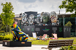"""© Licensed to London News Pictures. 21/07/2021. Stockport, UK.  The E7 , a Mount Rushmore-style sculpture also known as """" Mount Recyclemore """" , is unveiled outside the Stockport headquarters of recommerce company musicMagpie , who commissioned the sculpture for the G7 summit in June to much media interest . The sculpture was created out of e-waste in the likeness of the G7 leaders by artist and founder of the Mutoid Waste Company, Joe Rush , and will serve as an educational attraction during events hosted this summer , in collaboration with Totally Stockport and Stockport Council . Photo credit: Joel Goodman/LNP"""