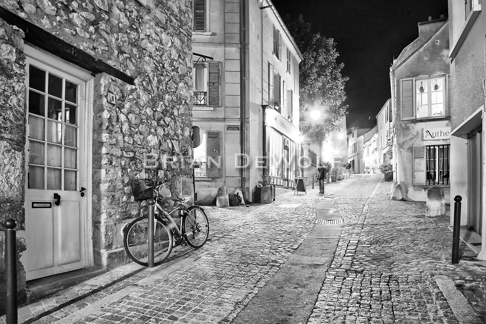 The fragrance of fine French cuisine wafts from the intimate little restaurants into the cool september night air.  A young woman stops to review the menu board. This is an intriguing tiny street in Marly le Roi, France.  Aspect Ratio 1w x 0.667h.