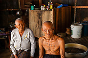 A Khmer/Cambodian veteran of the Southeast Asian War displays his tatttoos in his home.
