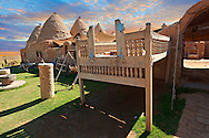 """Pictures of the beehive adobe buildings of Harran with a summer outdoor bed,  south west Anatolia, Turkey.  Harran was a major ancient city in Upper Mesopotamia whose site is near the modern village of Altınbaşak, Turkey, 24 miles (44 kilometers) southeast of Şanlıurfa. The location is in a district of Şanlıurfa Province that is also named """"Harran"""". Harran is famous for its traditional 'beehive' adobe houses, constructed entirely without wood. The design of these makes them cool inside. 31 .<br /> <br /> If you prefer to buy from our ALAMY PHOTO LIBRARY  Collection visit : https://www.alamy.com/portfolio/paul-williams-funkystock/harran.html<br /> <br /> Visit our TURKEY PHOTO COLLECTIONS for more photos to download or buy as wall art prints https://funkystock.photoshelter.com/gallery-collection/3f-Pictures-of-Turkey-Turkey-Photos-Images-Fotos/C0000U.hJWkZxAbg ."""