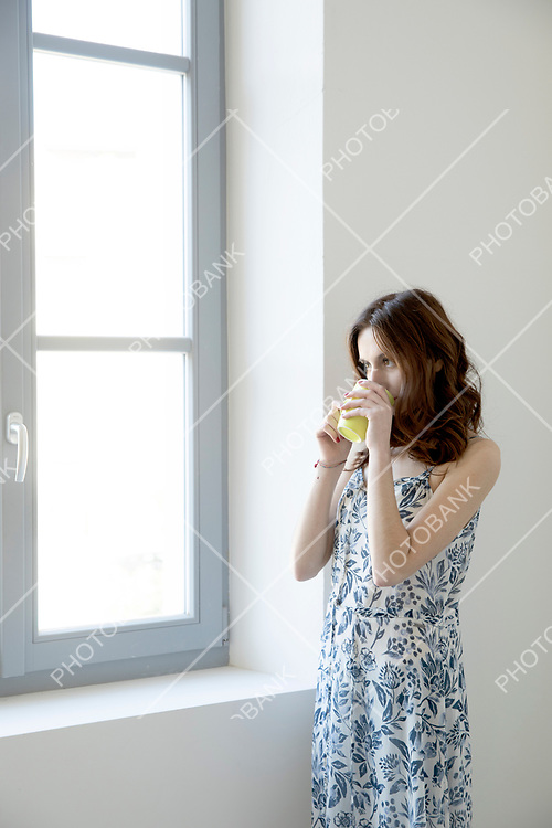 Brunette girl with long hair looks out the window with a yellow cup of tea. She looks out.