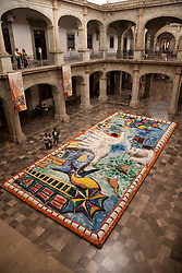 "North America, Mexico, Oaxaca Province, Oaxaca, Municipal Palace (Ex Government Palace), huge sand tapestry (Tapete de Areña).   These  ""carpets""  are made from sand, dyed sawdust, seeds, flower petals and powdered lime during annual Day of the Dead (Dias de los Muertos) celebration in November"