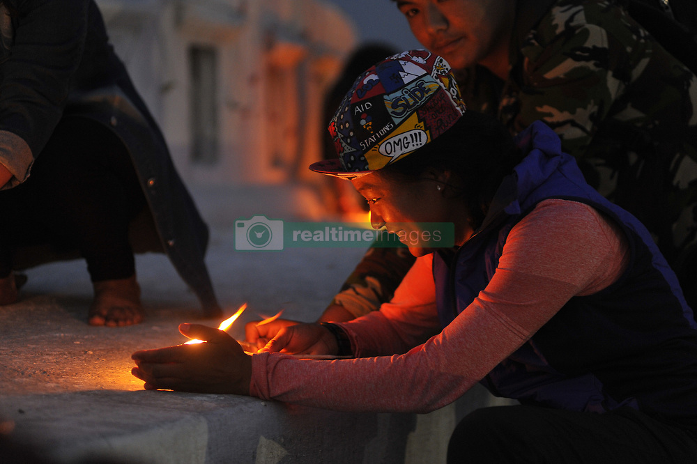 April 25, 2017 - Kathmandu, NP, Nepal - MIRA RAI, an athlete and the ultra-runner trail runner pays homage towards Earthquake victims on Second Anniversary by lighting up candles at Boudhanath Stupa, Kathmandu, Nepal on April 25, 2017. Most of monuments, old houses were badly destroyed by earthquake on April 25, 2015, a magnitude of 7.8 earthquake killing over 9,000 of people in Nepal and thousands of injured, which Outcomes Hundreds of people were homeless with entire villages across many districts of the country. (Credit Image: © Narayan Maharjan/Pacific Press via ZUMA Wire)