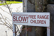 Road safety sign which reads: SLOW! Free Range Children in front of a tree in Wadebridge, Cornwall, UK.