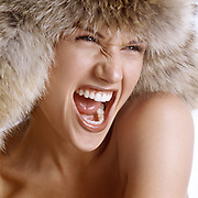 Close up of beautiful woman's face wearing a coyote fur hat and screaming