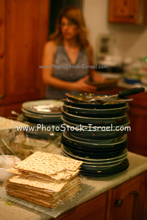 """An israeli family attending a """"Seder"""",  the traditional passover dinner,  and reading the """"Hagada"""" (the story of israeli's exodus from Egypt)  during the evening. A stack of dirty dishes after the meal"""
