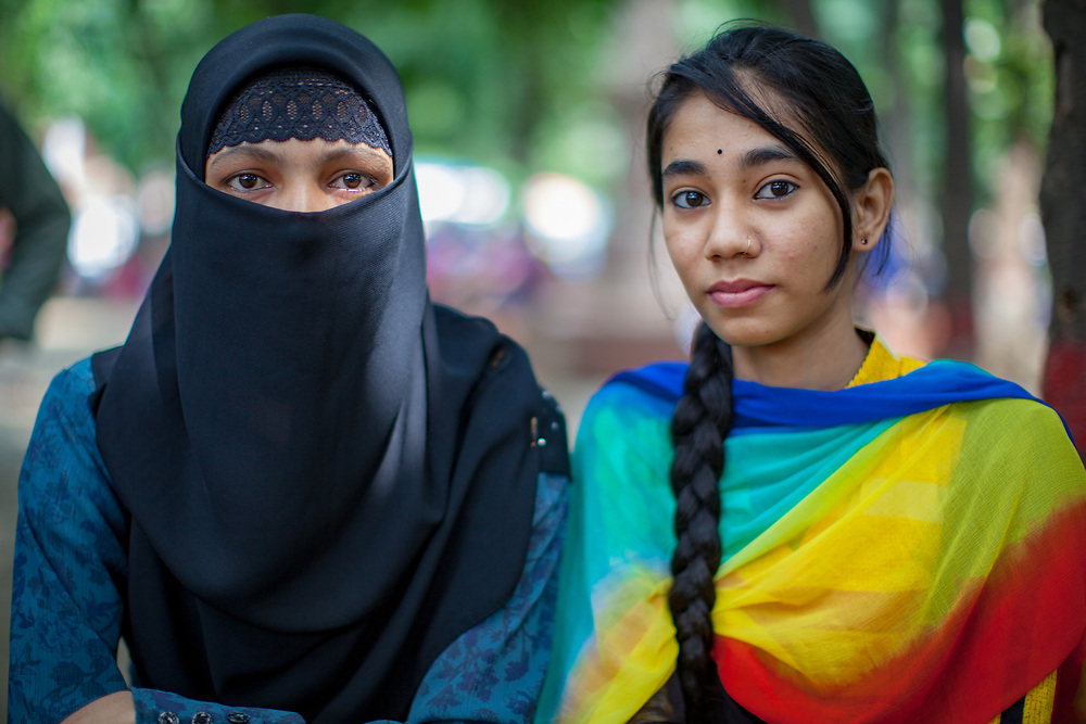 Two young women in old Dhaka, Bangladesh. One has a traditional black Niqab and the other is in a rainbow scarf.