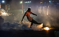 Baltimore, MD -- A protester kicks back a teargas canister as police push their line out into the street along North Avenue at Pennsylvania following a 10 PM curfew deadline firing teargas at protesters on the day after rioting following the death and funeral of Freddie Gray, a 25-year old black man who died in police custody.  -- Photo by Jack Gruber, USA TODAY
