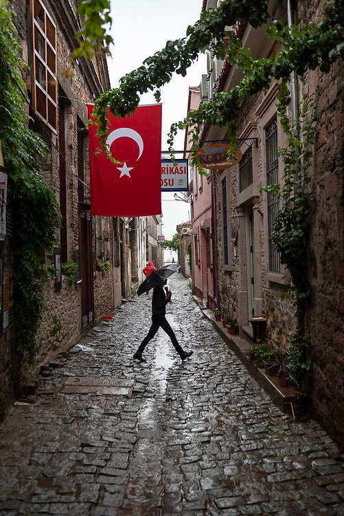 A man holding an umbrella on a rainy day walks in an alley beneath a large Turkish flag in Ayvalik, Turkey