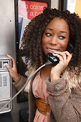 Young black woman using public telephone.