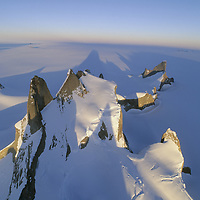 ANTARCTICA, Queen Maud Land.  Vista looking north over Filchner Mountains with midnight sun and shadows. Rakekniven spire is in right bkg. and Trolls Castle on left.