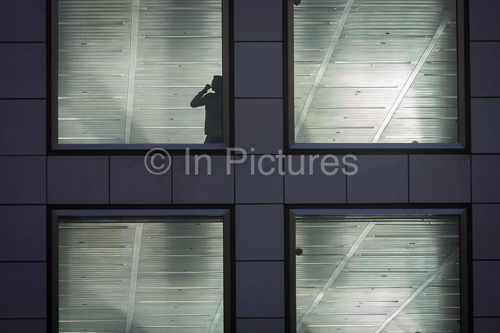 A man speaks on a handheld device at the window of a vacant office building in the City of London. With the phone to his ear, the decision maker speaks to arrange the completion of these new corporate floors, currently unoccupied by the tenant or owner and with fixtures, fittings and furnishings still to be fitted by the property's management. Work has yet to be completed before the hundreds or thousands of employees can move in to this building in the heart of the UK capital's financial district, founded by the Romans in AD43.