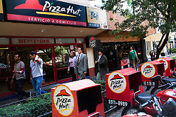 Pizza Hut deliver bikes are lined up outside of a Pizza Hut in Mexico City.