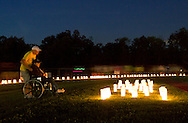 Goshen, New York - A man and woman look at luminaria set up inside the track, which is lined with more luminaria in remembrance of cancer victims, during the Relay for Life at Goshen High School on June 16, 2012. The Relay for Life is the American Cancer Society's signature fundraising event. Participants celebrate the lives of people who have battled cancer, remember loved ones lost, and fight back against the disease by raising money.