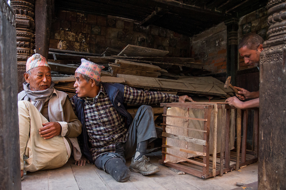 Men fashion a basket from lumber scraps in Bhaktapur Durbar Square. Ordinary earthquake debris, including lumber and bricks, is salvaged for reuse, while materials from historical sites are catalogued with an eye toward reconstruction.