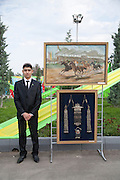 An art student stands next to his display at the City Hippodrome in Ashgabat on the occasion of National Turkmen Horse Day.