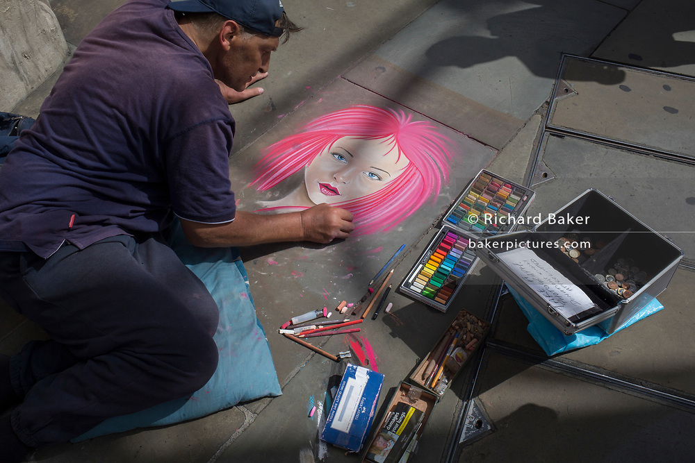 Street artist Nick C makes a pastel portrait of a girl on pink, for shoppers and pedestrians, on 31st July 2017, in Oxford Street, London, England.