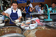 Mar. 8, 2009 -- BANGKOK, THAILAND: People in a food stall in the Chatuchak Weekend Market. The market covers an area of 35 acres with more than 15,000 shops and stalls. It has over 200,000 visitors each day it's open (Friday - Sunday), and they spend an estimated total of 30 million baht (approx US$750,000). The range of products on sale is extensive, and includes household accessories, handicrafts, religious artifacts, art, antiques, live animals (which unfortunately are frequently caged in cruel conditions), books, music, clothes, food, plants and flowers. Photo by Jack Kurtz / ZUMA Press