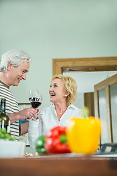 Mature couple holding glass of wine, smiling