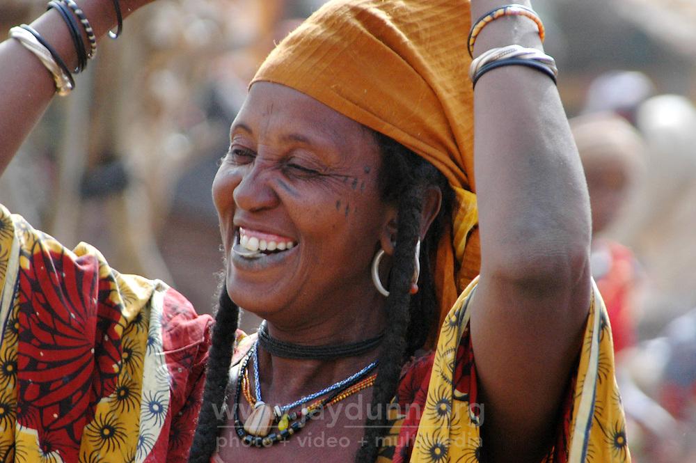 BURKINA FASO, Gorom-Gorom, 2007. A Fulani woman bites a Maria Theresa dollar coin as a joke to make sure it is real.