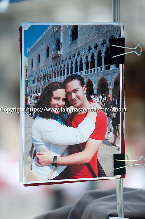 Detail of display sample photograph of tourists on souvenir photograph kiosk at San Marco Square in Venice Italy
