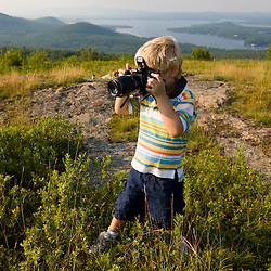 A young boy takes pictures on a hilltop in Alton, New Hampshire.