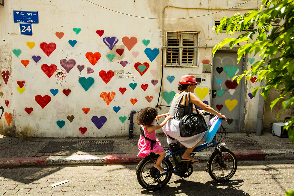 A woman rides her bicycle with her daughter past a graffiti covered wall in Tel Aviv's Kerem HaTeimanim neighborhood