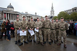 © Licensed to London News Pictures. 11/11/2013. London, UK. British Army Guardsmen watch a short film about an injured serviceman during the 'Silence in the Square' ceremony, held by the Royal British Legion in Trafalgar Square, London, today (11/11/2013). The ceremony, culminating in a two minutes silence and the placing of poppies into the square's fountains, is held on the 11th hour of the 11th day to commemorate the signing of the armistice that ended the First World War.  Photo credit: Matt Cetti-Roberts/LNP