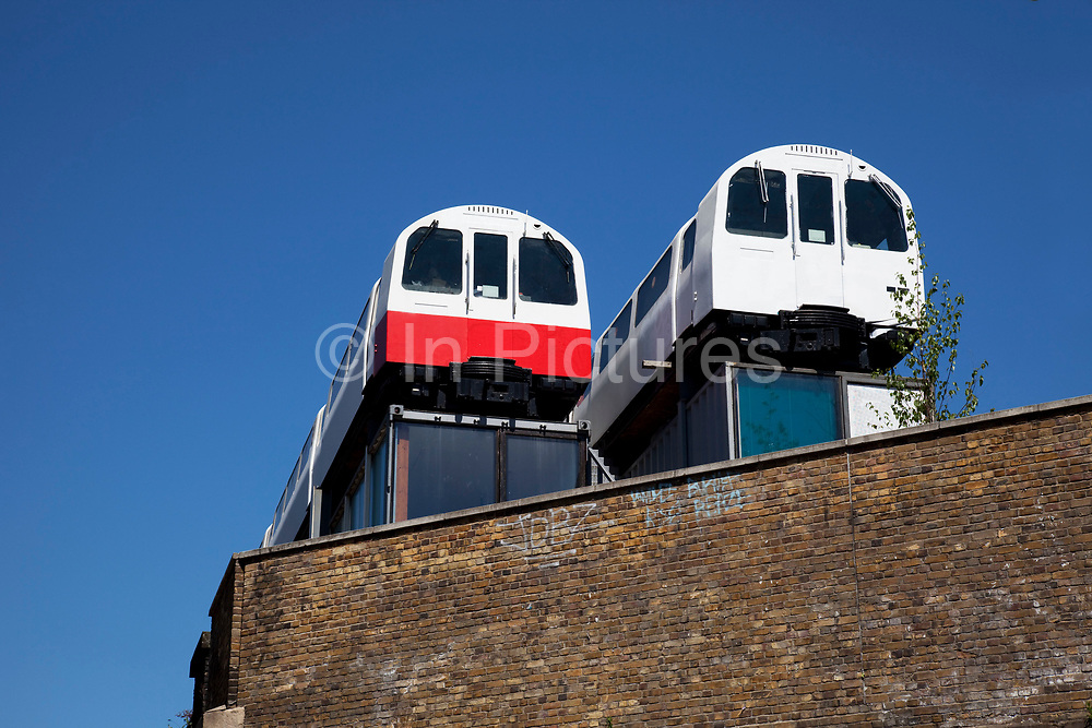 Two old London underground carriages sit atop an old railway arch in Shoreditch, East London. These old tube trains have been developed into offices. Time Out said: Walk along Great Eastern Street from Shoreditch High Street, look up, and you'll spot Village Underground's tube carriages atop a building. It cost designer and entrepreneur Auro Foxcroft £25,000 to get the 1983 Jubilee Line carriages up there by crane, with a plan to turn them into affordable, networking-friendly office space for creatives and small businesses.