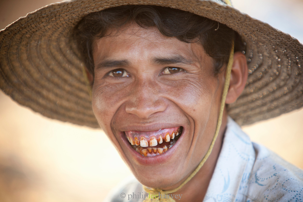 A ground nut farmer taking a break and eating betel nut, turning his mouth red, near Bagan in Myanmar