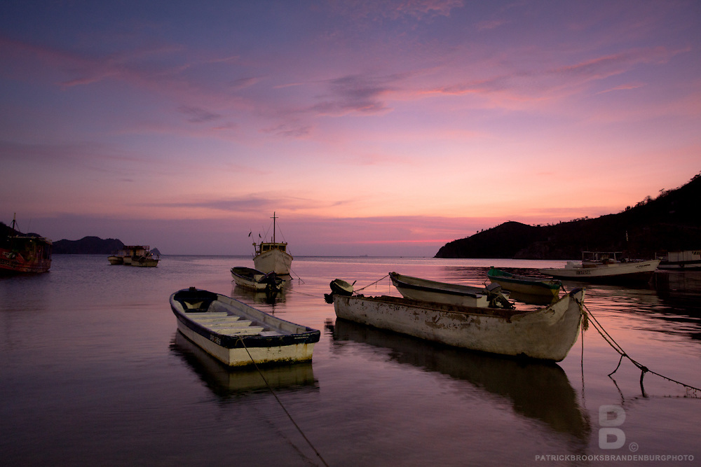 A red sunset in the sky lights up the water as street lights help fill in the boats with light avoiding a strong silhouette.