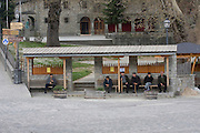 Greece, Epirus, Metsovo, Old men sitting on a bench at the square at the town's centre