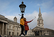 Two foreign women tourists make a selfie of themselves while standing on a wall opposite the church of St. Martins and the National Portrait Gallery, on 15th November 2017, in Trafalgar Square, Westminster, London, England.