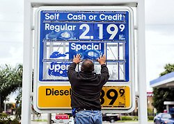 October 7, 2016 - Boynton Beach, Florida, U.S. - As things return to normal after Hurricane Matthew on Friday, Oct. 7, 2016, Al Gomez, manager of the Mobil gas station near Hypoluxo Road and Seacrest Boulevard, returns price information to the station's sign. ''We took the information down just as a precaution,'' Gomez said. (Credit Image: © Damon Higgins/The Palm Beach Post via ZUMA Wire)