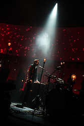 © Licensed to London News Pictures . 03/03/2013 . Manchester , UK . Jónsi Birgisson is illuminated by a single spotlight as around him the stage is filled with bare lightbulbs . Sigur Ros perform live at the 02 Apollo Manchester . Photo credit : Joel Goodman/LNP