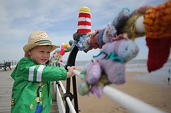 © Licensed to London News Pictures. 27/05/2013..Saltburn, England..Noah Jones, 3 from New Marske enjoys the display as once again the mysterious group of knitters in Saltburn by the Sea in Cleveland have been working their magic and have produced another amazing display of local seaside scenes created out of wool and attached to the Victorian Pier in the town...The woollen figures first appeared last year to mark the Olympics and then the royal wedding and created a storm of interest in the figures and brought many visitors into the town...Photo credit : Ian Forsyth/LNP
