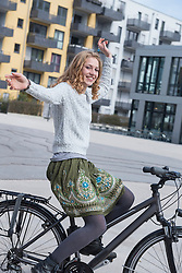 Young woman performing stunt on bicycle, Munich, Bavaria, Germany