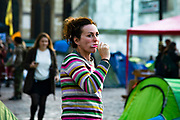 A woman camped outside the Westminster Abbey ,brushes her teeth on 8th October, 2019 in London, Untited Kingdom. Extinction Rebellion plan to occupy 12 sites situated around key Government locations around Westminster for two weeks to protest against climate change.