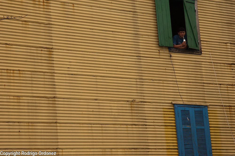 A man drinks mate while leaaning on a window at Caminito street, in La Boca neighborhood of Buenos Aires, Argentina.<br /> Caminito is a pedestrian street created in the late 1950s by local painter Benito Quinquela Martín and other artist friends to recreate a version of the old immigrant neighborhood of La Boca, using wood and corrugated zinc painted in bright colors. Today, Caminito and the surrounding areas feature cafes, souvenir shops, tango dancers and other street performances aimed to attract tourists.