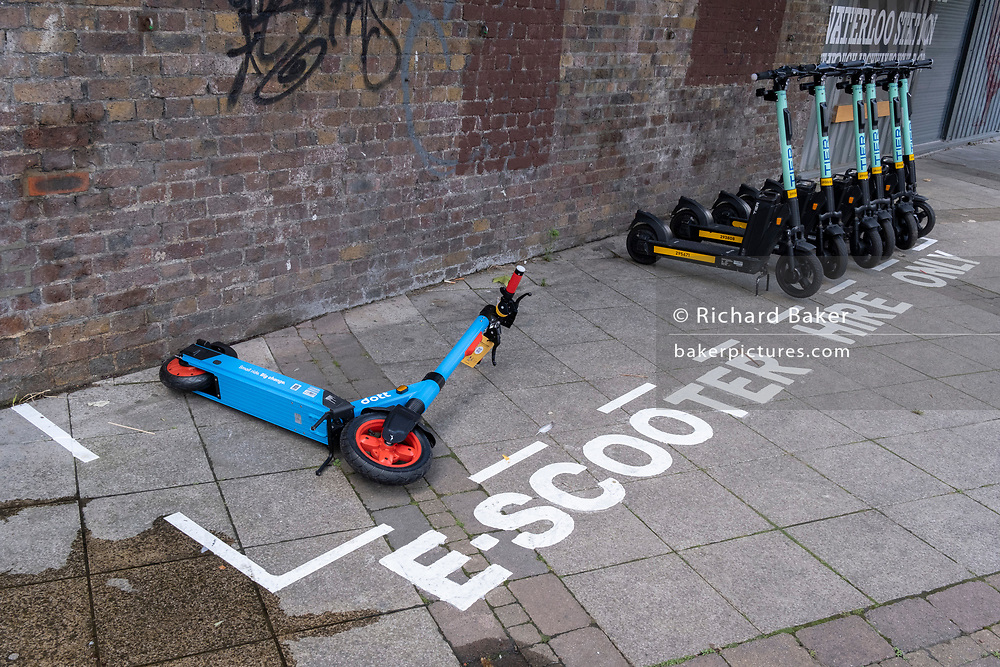 A Dott eScooter has fallen over alongside still-standing Tier scooters, all placed within a special area for licensed and therefore legal rental eScooters, in Waterloo, SE1, on 8th July 2021, in London, England.