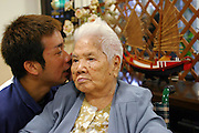 """Mie Ohshiro, 100 years old and slightly deaf, listens intently as 28-year-old nursing home aid Satoru Yamanoha repeats a question posted by a visitor about this Naga City Okinawa day care facility. """"I enjoy it because I have lots of friends here,"""" she says, """"and my son and his wife also use this place."""" Mie lives with her second son and his family but comes to the center two or three times a week for a traditional Okinawan lunch, physical therapy, and companionship."""