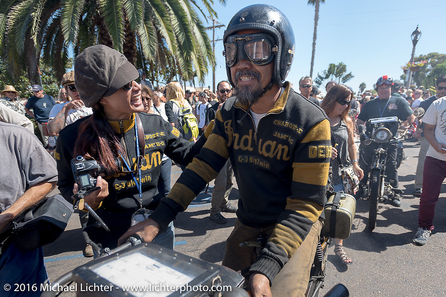 Shinya Kimura is greeted by his wife Ayu Yamakita as he rides over the finish in Carlsbad, CA on his Team-80 1915 Indian twin during the Motorcycle Cannonball Race of the Century. Stage-15 ride from Palm Desert, CA to Carlsbad, CA. USA. Sunday September 25, 2016. Photography ©2016 Michael Lichter.