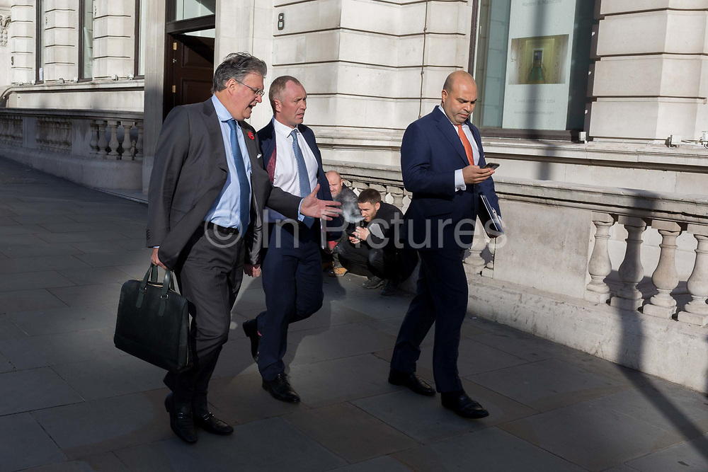 Three businessmen walk past a vaping contractor sat on the ground on Haymarket, on 13th November 2018, in London, England.